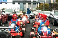 信号待ちの間に車両から降り、写真撮影をするカートの集団=4月、東京都千代田区(加藤園子撮影、画像の一部を処理しています)