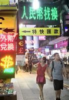 香港市内にあふれる、中国の通貨「人民元」両替ブースの前を歩く男女=5日(河崎真澄撮影)