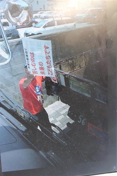 トラックとトラックの間で「苦しむのは未来のこどもたちです」と書かれたプラカードを掲げる基地移設反対派=4月21日、沖縄県名護市東江(トラック運転手の男性が事故直前に動画で撮影)