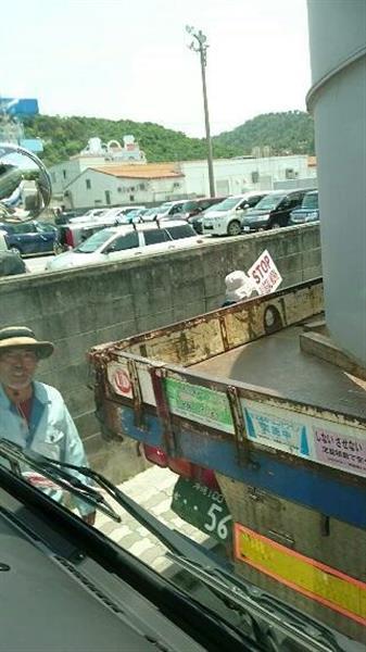 トラックとトラックの間で抗議の声を上げる反対派の男性(麦わら帽子姿)=4月21日、沖縄県名護市東江(トラック運転手の男性が運転席から事故直前に撮影)