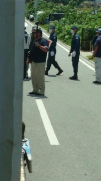 トラックの周囲で抗議の声を上げる反対派とそれを取り囲んで牽制する警察官=4月21日、沖縄県名護市東江(トラック運転手の男性が事故の直前に運転席から撮影)