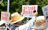 沖縄全戦没者追悼式の会場外で、基地反対などのプラカードを掲げて抗議する人ら=23日、沖縄県糸満市(今仲信博撮影)