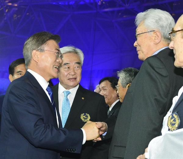 テコンドー世界選手権大会の会場で、北朝鮮の張雄IOC委員(右)と握手する韓国の文在寅大統領=24日、韓国中部、茂朱(聯合=共同)
