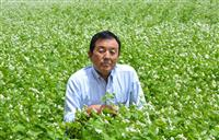夏ソバの白い花が咲く畑で全国一のソバを目指す高井さん=渋川市赤城町