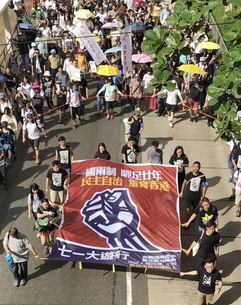 中国返還から20年となった1日、香港中心部で「一国二制度」の危機などを訴えて行進した民主派のデモ隊。主催した民主派団体「民間人権陣線」の区諾軒代表らは黒いTシャツを着て「中国の政治は北朝鮮と何ら違わない。香港の『一国二制度』は死んだも同然」と叫んだ(河崎真澄撮影)