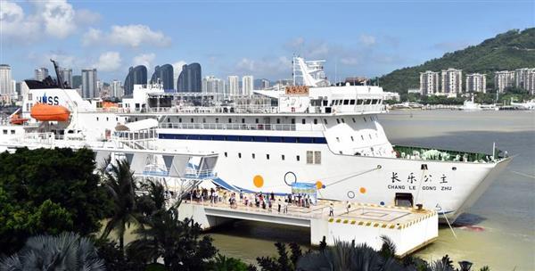 パラセル諸島に向かう定期クルーズ船の埠頭で記念撮影する乗客ら=9日、中国海南省三亜