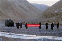 カシミール地方ラダックで、国境侵犯を警告する横断幕を掲げる中国軍兵士=2013年5月(AP)