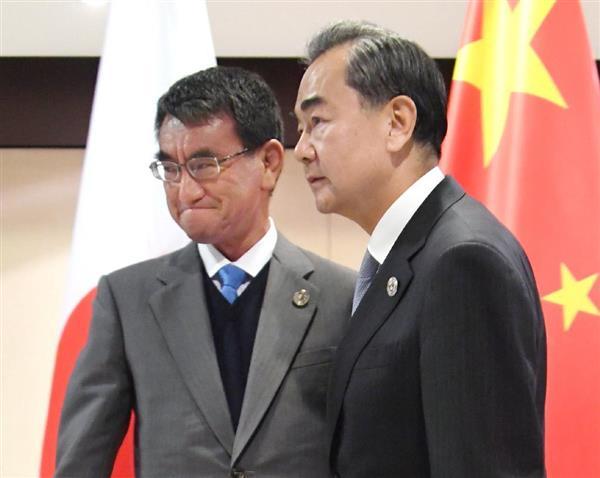 会談に向かう河野外相(左)と中国の王毅外相=7日、マニラ(共同)