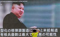 北朝鮮の核問題を報じる街頭テレビを撮影する男性=9日、東京(AP)