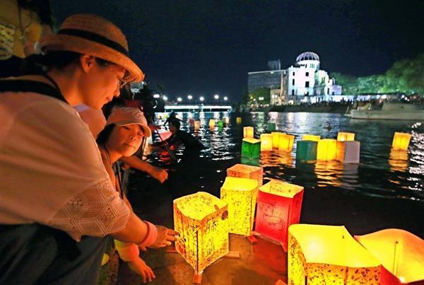 8・6原爆忌、元安川に灯籠を流す親子連れら=6日夜、広島市の平和記念公園(鳥越瑞絵撮影)