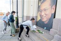 オスロにあるノーベル平和賞や受賞者を紹介する施設で、劉暁波氏の写真の前に花を置く女性ら。ノルウェー政府は劉氏の治療や死去をめぐる問題で目立たぬ姿勢に徹した=7月13日(ロイター)