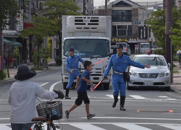信号が点灯しなくなったため手で誘導する警察官=23日午前9時2分、大阪府吹田市 (安元雄太撮影)