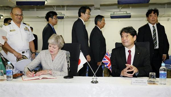 海自護衛艦「いずも」で、乗艦の記帳をする英国のテリーザ・メイ首相(左)。右は小野寺五典防衛相=31日午前、神奈川県の海上自衛隊横須賀基地(代表撮影)