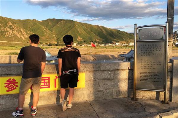 中国・図們市から対岸の北朝鮮をながめる人たち=30日(ロイター)