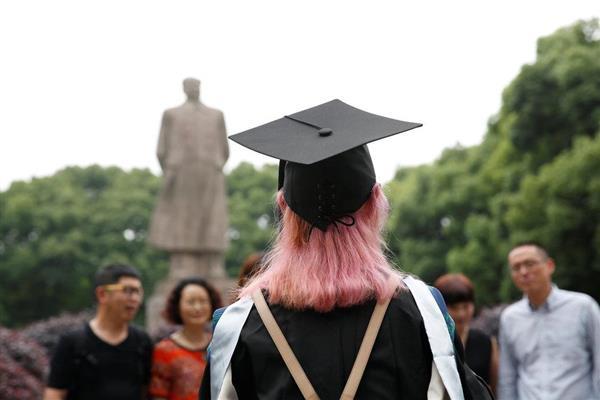 中国・上海で毛沢東像の前に立つ大学生。オーストラリアでは中国政府の意見を代弁するかのように中国人学生が教師を批判するケースが相次いでいる(ロイター)