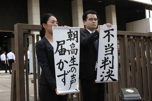 朝鮮学校無償化訴訟で原告敗訴となり、原告側が「不当判決」と書かれた幕を掲げた=13日午後、東京地裁前