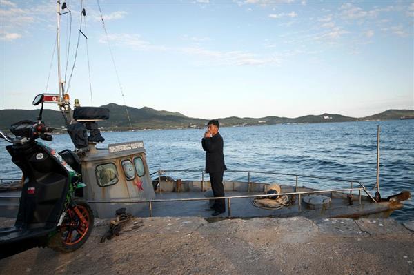 観光船の上でたばこを吸う男性=12日、北朝鮮の羅先特別市の羅津港(AP)