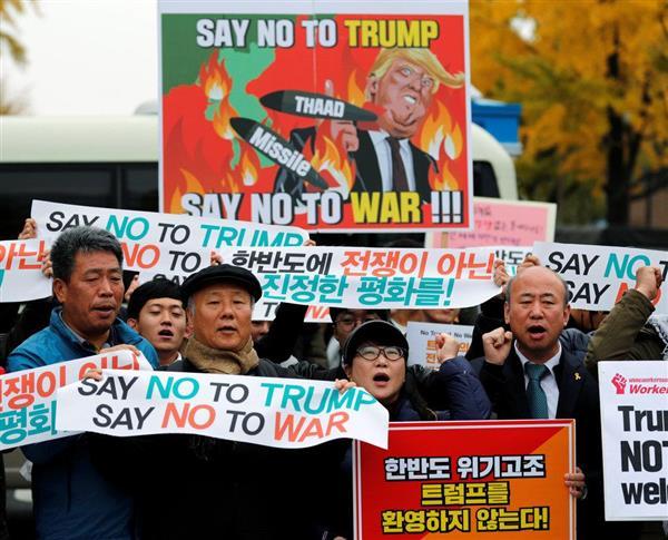 ソウルの大統領官邸近くで、トランプ米大統領の訪韓に抗議する人たち=7日(ロイター)