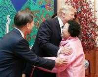 韓国大統領府での夕食会で、抱き合ってあいさつするトランプ米大統領(中央)と元慰安婦の李容洙さん。左は文在寅大統領=7日、ソウル(聯合=共同)
