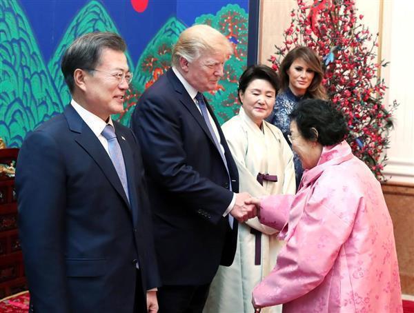 韓国大統領府での夕食会で握手するトランプ米大統領(中央)と元慰安婦の李容洙さん。左端は文在寅大統領=7日、ソウル(聯合=共同)