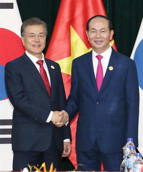 11日、ベトナム中部ダナンで会談し、握手する韓国の文在寅大統領(左)とベトナムのチャン・ダイ・クアン国家主席(聯合=共同)