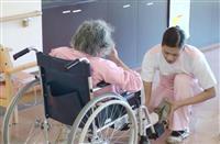 介護施設で入所者を介助する外国人スタッフ