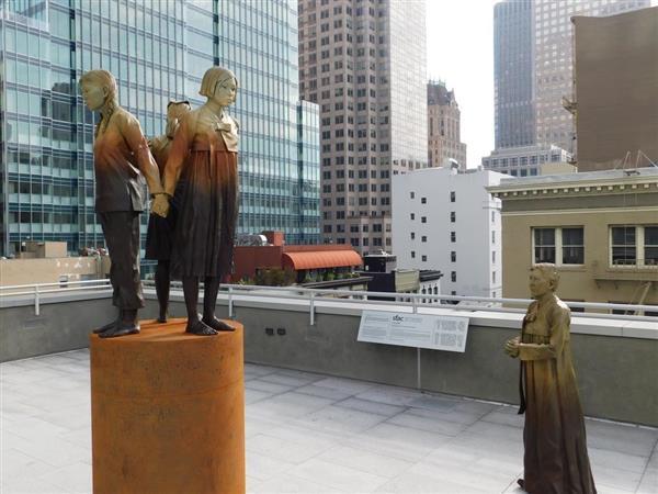 サンフランシスコ市のセントメリーズ公園に設置された慰安婦像と碑文。3人の女性が背中合わせに立ち、傍で慰安婦とみられる女性が見つめる構図となっている=22日、米サンフランシスコ