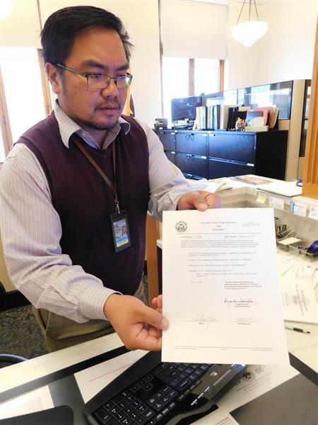 市議会決議案について、エドウィン・M・リー市長が受け入れを認める署名をした文書を持つ市議会事務局の職員。一番下に市長の署名がある=22日、米サンフランシスコ市のシティホール