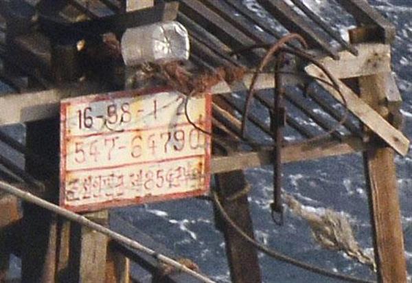北海道松前町沖に浮かぶ北朝鮮船に掲げられたプレート。3段目に「朝鮮人民軍第854軍部隊」との表記があった=11月29日(共同通信社機から)