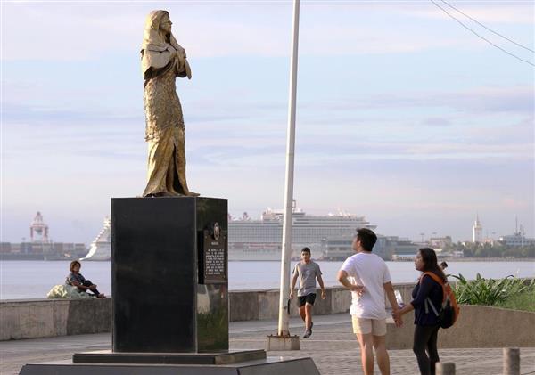 フィリピンのマニラ湾に面した遊歩道に建った慰安婦像を見つめる人々(吉村英輝撮影)