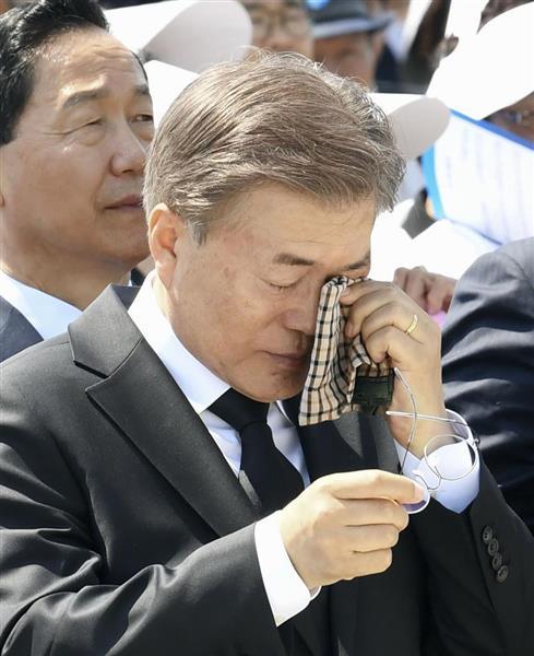 光州事件の式典で、犠牲者遺族のメッセージに涙ぐむ韓国の文在寅大統領=2017年5月、韓国・光州(共同)