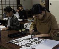 真剣な表情で書をしたためる子供たち=和歌山県海南市