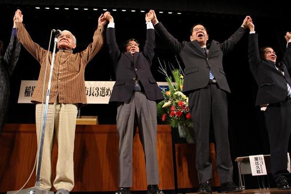 市民集会で、手をつないでガンバロー三唱を行う稲嶺進氏(左から2人目)と共産党の志位和夫委員長(同3人目)=12日、名護市(八重山日報提供)