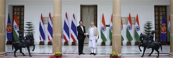 25日、ニューデリーで行われたインド・ASEAN首脳会議に先立ち握手するモディ印首相(右)とタイのプラユット首相(AP)