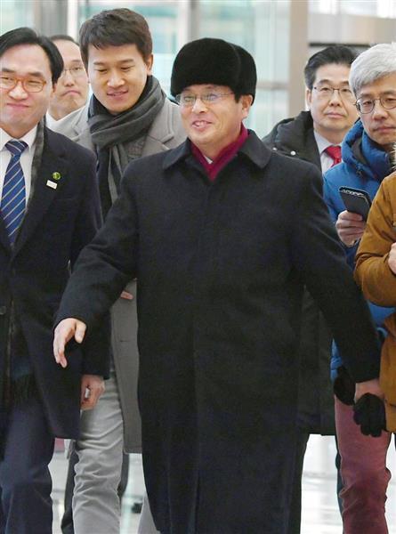 27日、韓国での全日程を終え北朝鮮に戻る、北朝鮮代表団先発隊のユン・ヨンボク体育省副局長。記者団の質問に笑顔を浮かべた=ソウル北方の都羅山(共同)