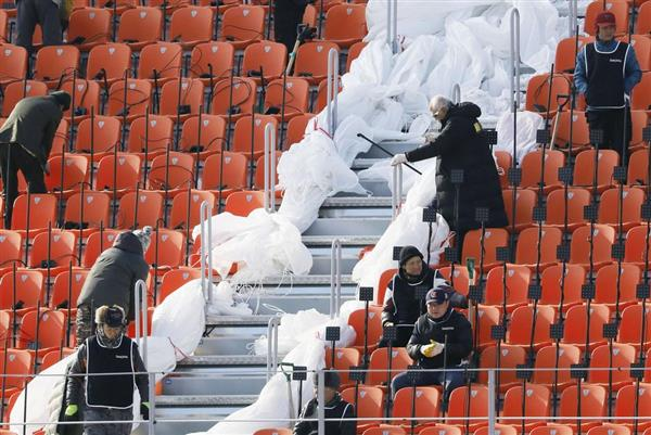 開会式が行われる平昌五輪スタジアムの客席スタンドで、厚着をして作業する関係者=1月28日、韓国・平昌(共同)