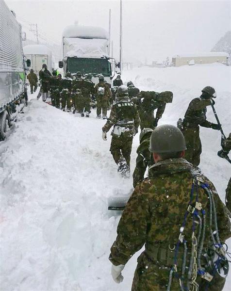立ち往生した車の周囲で除雪作業をする陸上自衛隊員=7日、福井県あわら市(陸上自衛隊金沢駐屯地提供)