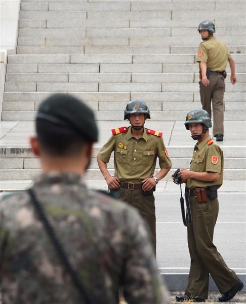 板門店で南北軍事境界線を挟みにらみ合う北朝鮮の朝鮮人民軍将校(奥)と韓国軍兵士=2017年7月(共同)
