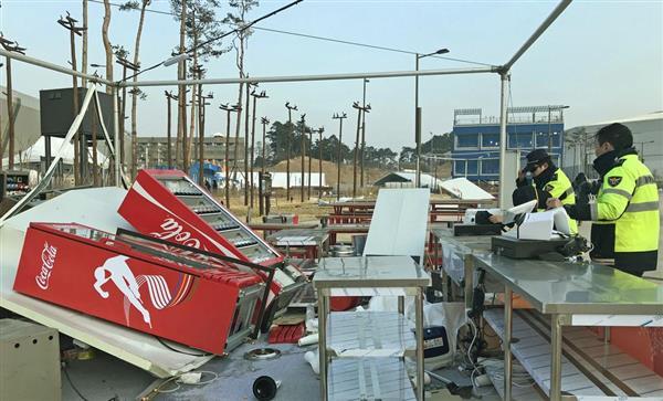 強風で冷蔵庫が倒されるなど、物が散乱した五輪公園内の店舗。右は巡回する警察官=14日、韓国・江陵(共同)