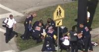 銃撃事件の負傷者を手当てする救急隊員ら=14日、米フロリダ州パークランド(WSVN提供・ロイター=共同)