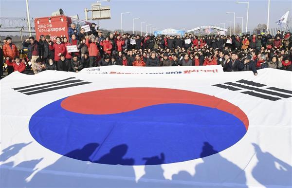 北朝鮮の金英哲朝鮮労働党副委員長らの訪韓に抗議する集会で、韓国国旗の前に座り込む野党国会議員ら=25日、韓国・坡州(共同)