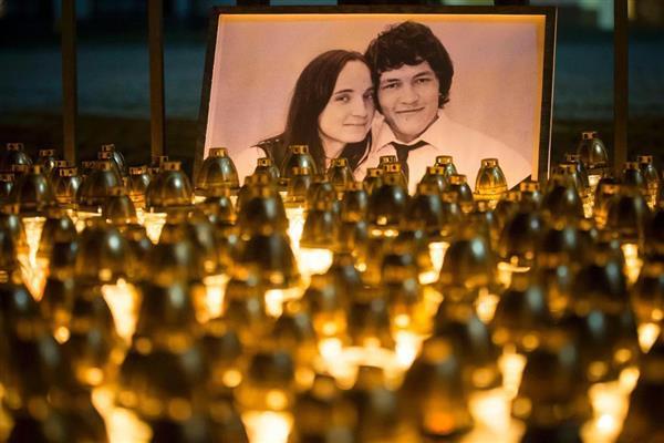 2月28日、スロバキアの首都ブラチスラバで飾られたヤン・クツィアク氏(右)と、ともに射殺体で発見された交際相手の女性の遺影 (AP)