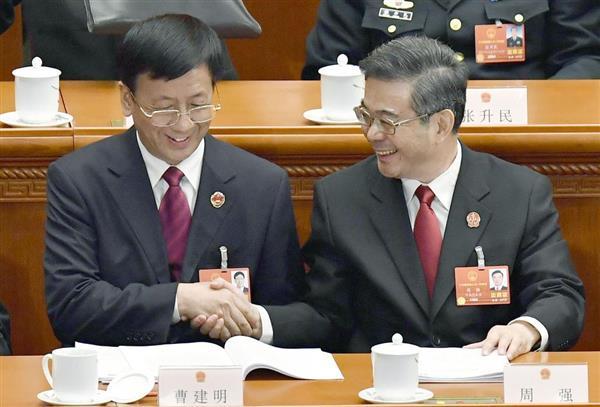 全人代で握手する中国最高人民検察院の曹建明検察長(左)と最高人民法院の周強院長=9日、北京の人民大会堂(共同)