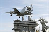 米海軍の原子力空母カール・ビンソンの艦橋と訓練飛行するFA18戦闘攻撃機=16日午後、沖縄本島から東南東沖の太平洋上(共同)