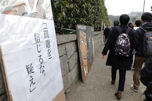 京大の文化と言われる立て看板の脇を足早に試験会場へと急ぐ受験生ら。「(問題を)信じるな」と書かれている=京都市左京区の京都大