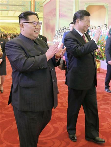 26日、北京の人民大会堂で開かれた夕食会で、芸術団に拍手する北朝鮮の金正恩朝鮮労働党委員長(左)と中国の習近平国家主席(朝鮮中央通信撮影・共同)