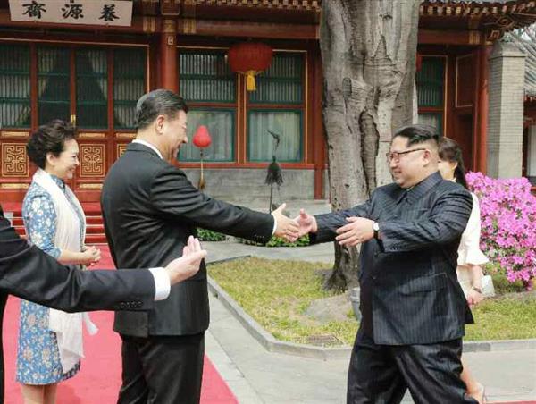 3月27日、北京の釣魚台迎賓館で中国の習近平国家主席(左から2人目)に両手を差し伸べる北朝鮮の金正恩朝鮮労働党委員長。労働新聞が28日掲載した(コリアメディア提供・共同)