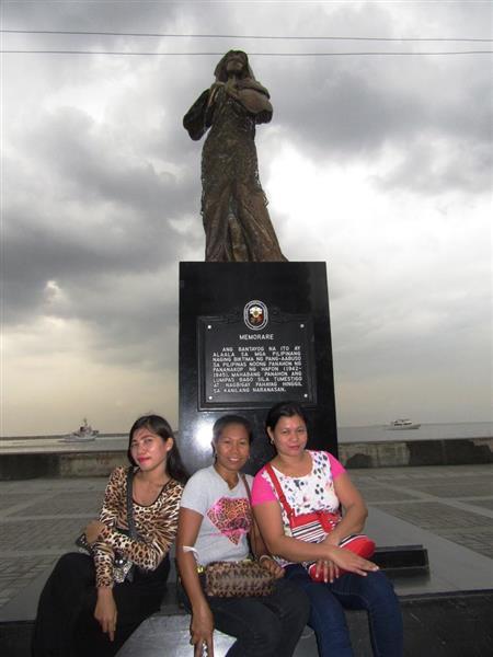 5日、マニラで慰安婦を象徴するとする女性像の前でポーズをとる女性たち