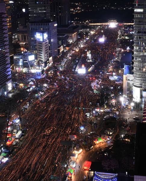 朴槿恵政権の退陣を求めソウル中心部で行われたろうそくデモ=2016年12月10日(長時間露光、共同)