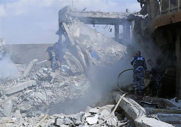 市民への化学兵器使用が疑われるバッシャール=アル・アサド大統領側へ行われた、懲罰的な米英仏のミサイル攻撃で破壊されたシリア科学研究センターから発生する煙を消す消防士ら=14日、ダマスカス近郊(AP)